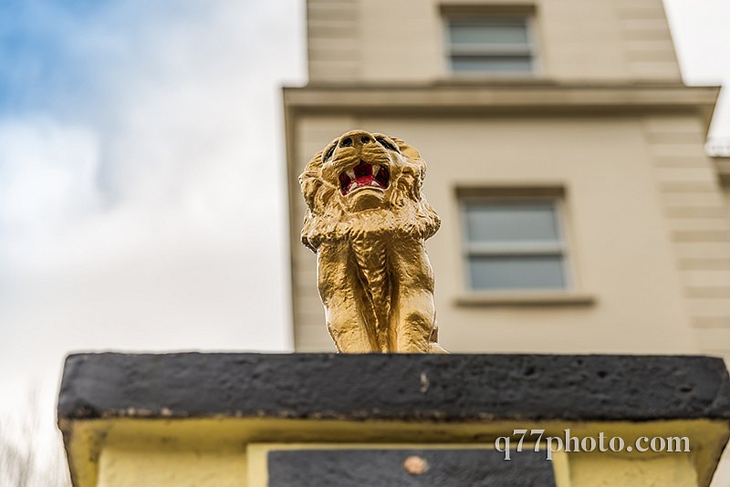 view from below on a gold lion on a pedestal in front of the gat