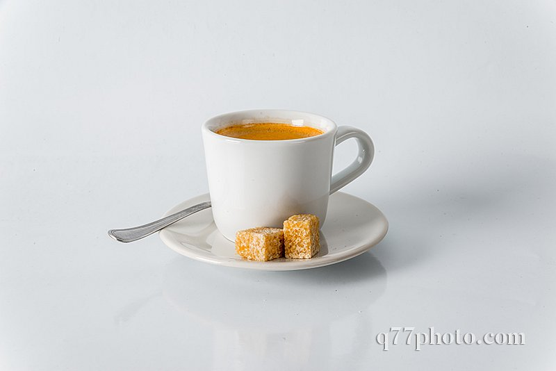Black coffee in white cup, brown sugar cubes on saucer