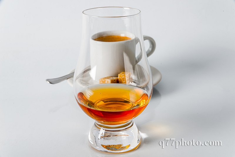 Black coffee in white cup, brown sugar cubes on saucer, whisky s