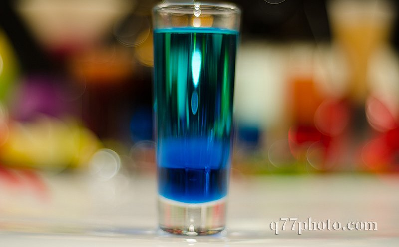 colored drink in glass for shots, a combination of green with bl