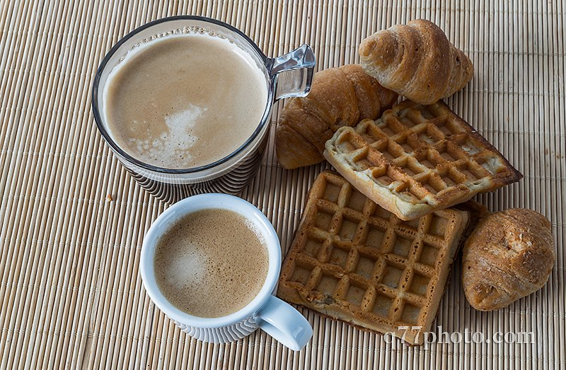 Fresh croissants and delicious waffles with two coffee on bamboo