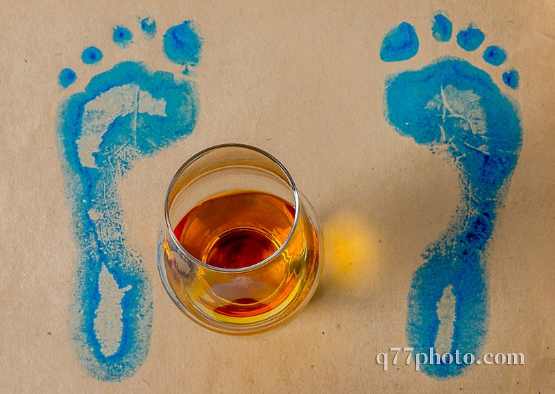 The glass of single malt whiskey, gray paper with blue footprint