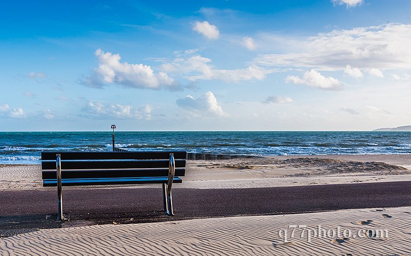 Beautiful seaside view, sandy beach, bench, blue sky, ocean and