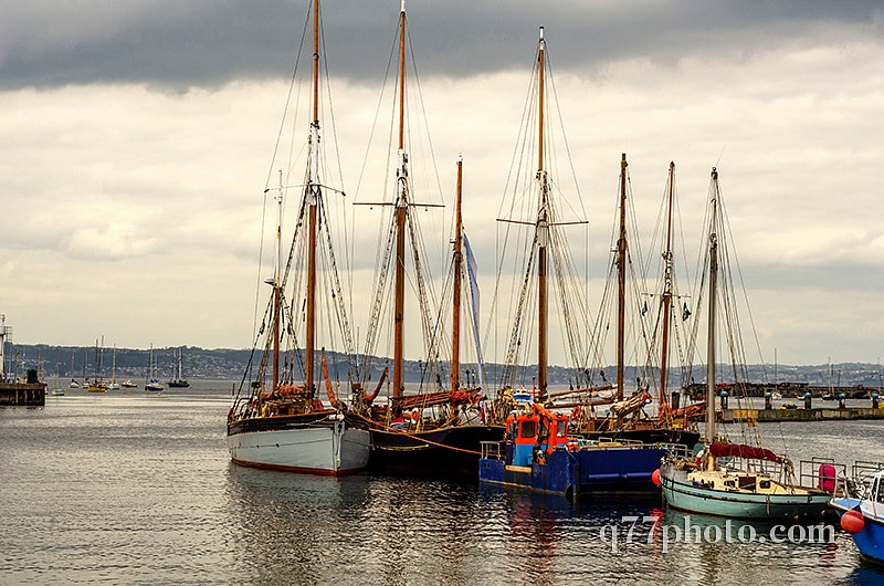 Boats anchored in a harbor, in the background stone promenade, s