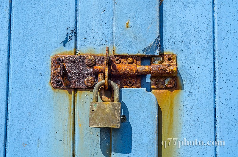 Old rusty padlock on wooden doors, old blue destroyed door, rust