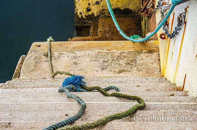 Descent down to the ocean in a fishing port, old cords and ropes